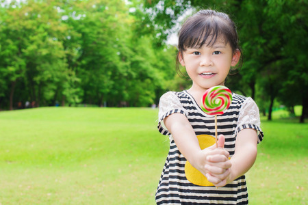 5 years: Asian little girl eating lollipop outdoors in spring park