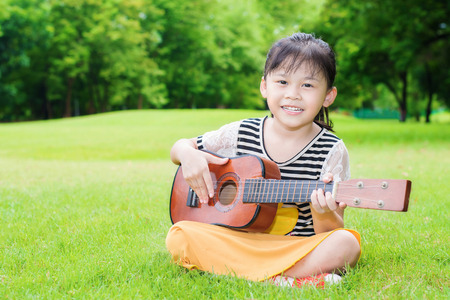 Asian little girl sitting on grass and play ukulele in park Stock Photo