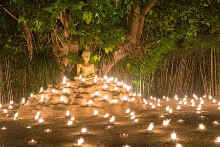 bouddha: Bouddhistes bougies moine d'incendie au Bouddha avec une belle réflexion de l'eau à Phan Tao Temple, Chiangmai, en Thaïlande Banque d'images