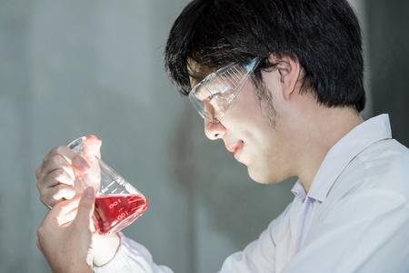 estudiantes medicina: científico asiático en uniforme blanco mirando a un vaso de precipitados de ensayo en laboratorio