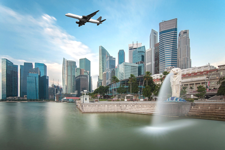Travel, Transportation concept - Airplane flying over Singapore city in morning time