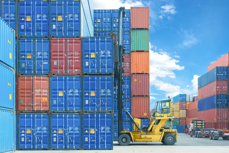lift truck: forklift handling container box loading to truck in import export logistic zone