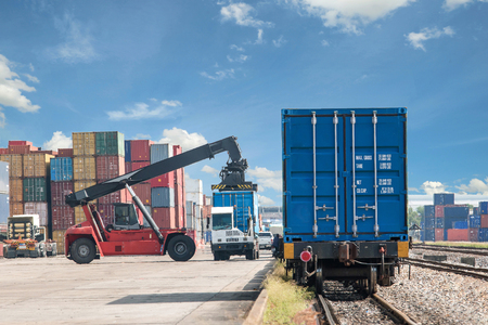container port: forklift handling container box loading to freight train