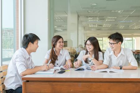 scuola: Gruppo di studenti asiatici in uniforme che studiano insieme a aula