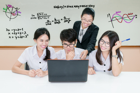 asian boy: Asian teacher assisting student using laptop at desk in classroom Stock Photo