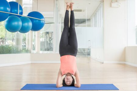 headstand: Asian woman make yoga Supported headstand pose in classroom
