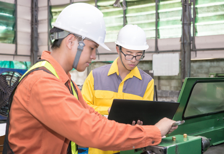 safety device: Asian Mechanical Engineer using computer-aided to do planning and control equipment in factory Stock Photo