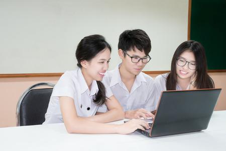 aula: Grupo de estudiante asiática en uniforme de e-learning a través del ordenador portátil en el aula