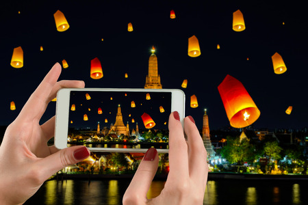 Back view of a woman taking photograph with a smart phone camera at Wat arun under loy krathong day ,Thailand