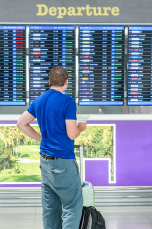 arrival: Young man with backpack in airport near flight timetable Stock Photo