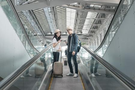 mochila de viaje: Joven pareja asiática con el equipaje por las escaleras mecánicas en el aeropuerto