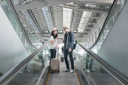 backpackers: Young asian couple with luggage down the escalator in airport