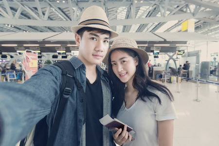 Asian couple tourist taking a selfie in airport before journey Stock Photo