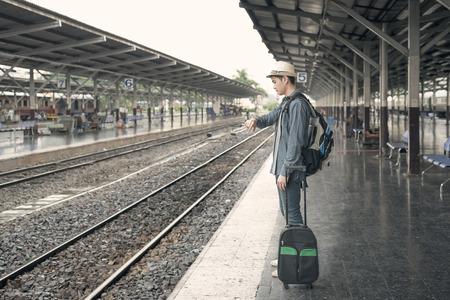 plataforma: retraso de tren. Hombre asiático joven que mira en su reloj mientras espera el tren en la estación