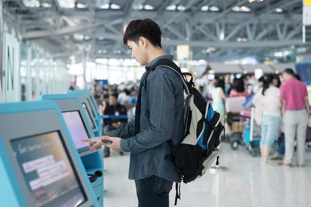 gente aeropuerto: Hombre asiático joven que usa el auto kioscos de check-in en el aeropuerto