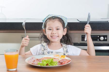 petit dejeuner: la famille, les enfants et les gens heureux Concept - fille asiatique enfant de manger le petit d�jeuner am�ricain dans la maison