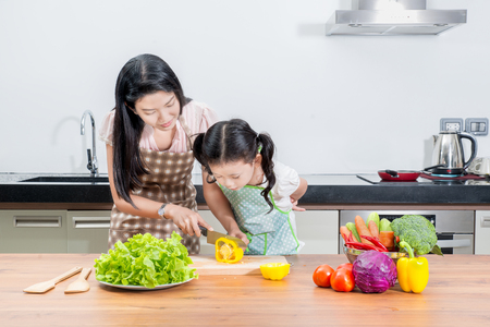 asian chef: family, children and happy people concept - Asian mother and kid daughter cooking in the kitchen at home
