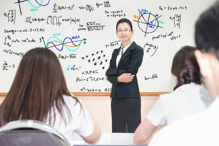 professors: Asian teacher with a group of high school students in classroom