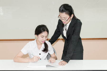 thai student: Teacher guide something to Asian student in uniform at classroom Stock Photo