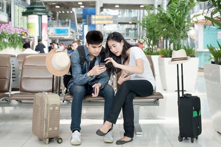 gente aeropuerto: Pareja joven de Asia con teléfono inteligente mientras se está sentado en la terminal del aeropuerto a la espera de embarque.