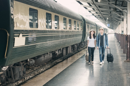 Couple of Asian tourists waiting train in station