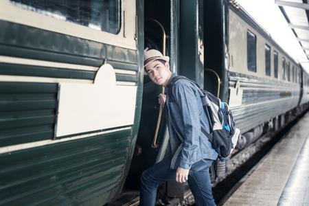 mochila de viaje: Apuesto hombre asiático joven en una estación de tren Foto de archivo