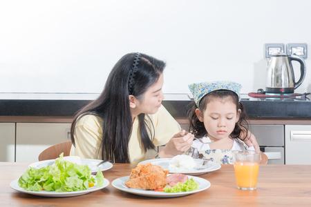 ni�os desayuno: cabritos de la muchacha asi�tica con expresi�n de disgusto contra comen arroz mientras que el desayuno de alimentaci�n madre Foto de archivo