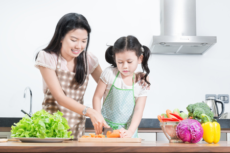 preparing food: family, children and happy people concept - Asian mother and kid daughter cooking in the kitchen at home