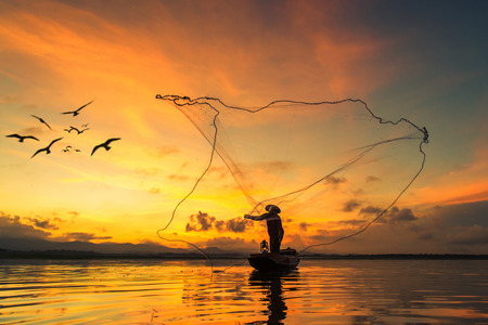 Fisherman fishing at lake in Morning, Thailand. Zdjęcie Seryjne