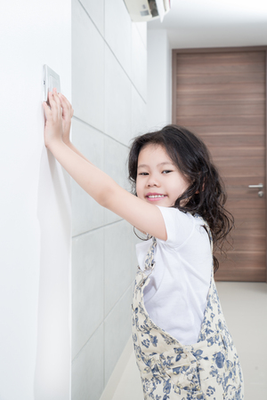Environmental Issues concept - Asian little girl turn offon switch of light Stock Photo