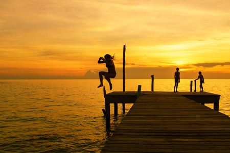 pier: Silhouettes of woman jump into sea from pier