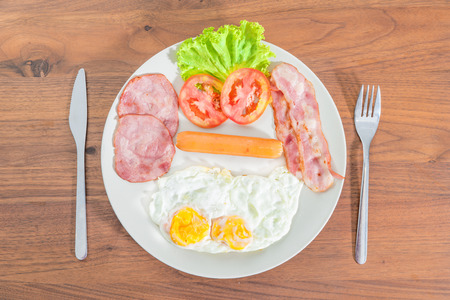 bacon and eggs: English breakfast with fried eggs, bacon, sausages, ham and fresh salad