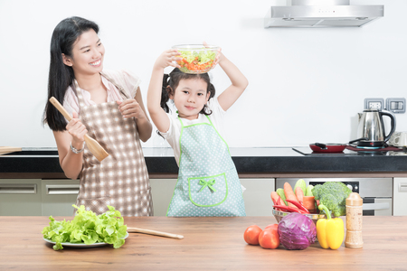 niños cocinando: familia, los niños y la gente feliz concepto - Asia madre e hija niño en la cocina en el hogar