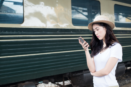 using phone: Asian woman texting on smartphone at train station with railway in background Stock Photo
