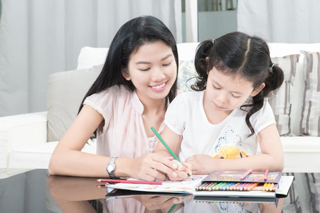 teaching children: family, children and happy people concept - mother and daughter drawing at home Stock Photo