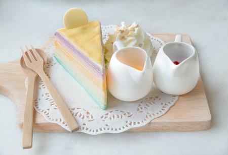 cake plate: Rainbow crepe cake with sauce on wood plate