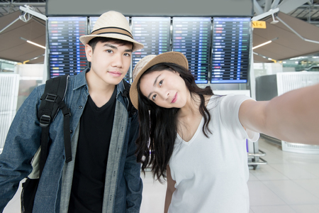 airports: Asian couple tourist taking a selfie in airport before journey Stock Photo