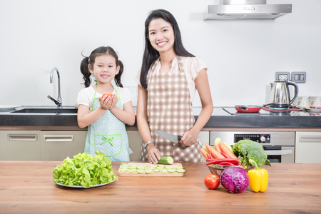 mom: family, children and happy people concept - Asian mother and kid daughter cooking in the kitchen at home