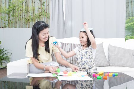 family, children and happy people concept - Asian mother and kid daughter playing with plasticine in home
