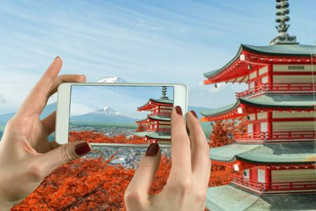 buddhist's: Back view of a woman taking photograph with a smart phone camera at Mt. Fuji with fall colors in Japan.