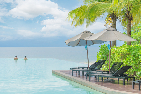 Summer, Travel, Vacation and Holiday concept - Umbrella and chair with pool in hotel resort