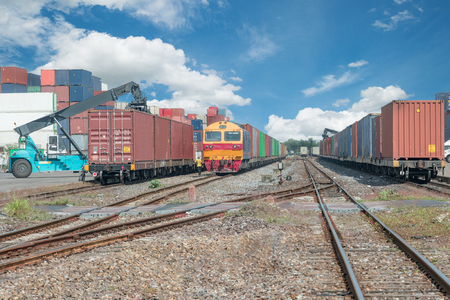 Cargo train platform with freight train container at depot Imagens