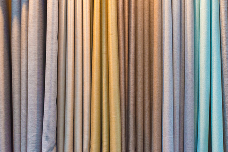 sample: Colorful curtain samples hanging from hangers on a rail in a display in a retail store Stock Photo