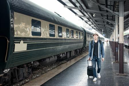 Młody azjatycki turysta z bagażem czeka pociąg na stacji. Zdjęcie Seryjne