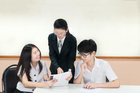 uniforme: Los maestros gu�an algo para pareja estudiante asi�tico en uniforme en el aula