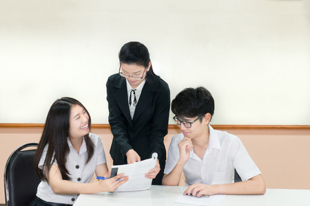 thai teen: Teachers guide something to Couple asian student in uniform at classroom