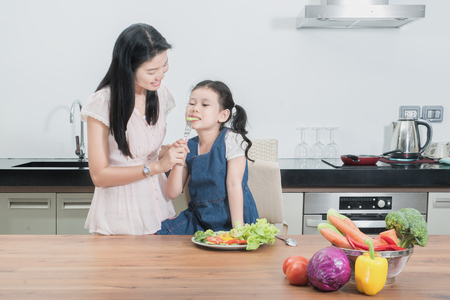 feed: Asian mother feeding kid daughter vegetables in kitchen