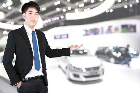car showroom: Asian salesman in car showroom Stock Photo