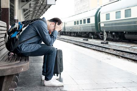 estacion de tren: Asia viajero deprimida espera en la estación de tren después de los errores de un tren Foto de archivo