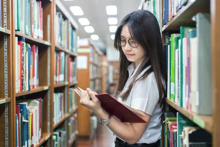 Allievo asiatico in lettura uniforme nella biblioteca all'università